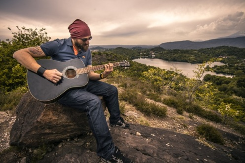 Man playing guitar in nature: is he talented or just a hard worker?