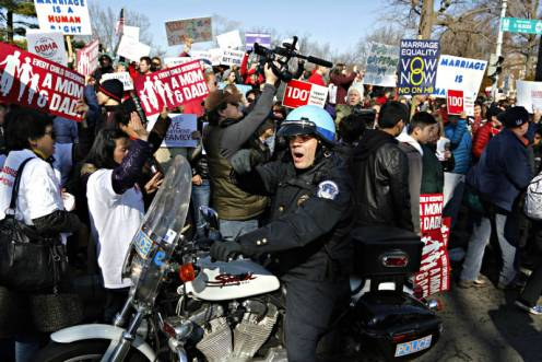 a-policeman-pushes-anti-gay-marriage-protesters-from-the-street-in-front-of-the-u-s-supreme-court-in-washington-march-26-2013